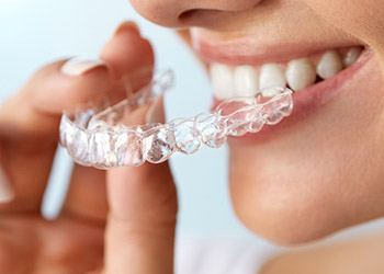 Patient placing Invisalign tray