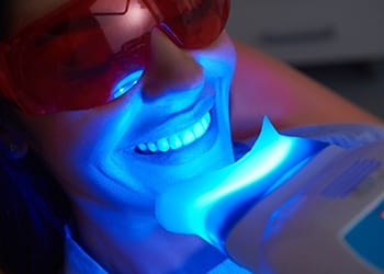 Woman smiling during teeth whitening treatment