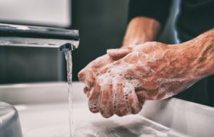 Man washing hands according to dentist
