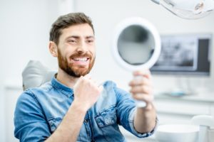 patient admiring his smile after seeing his cosmetic dentist in Falls Church